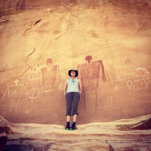 woman stands by a pictograph