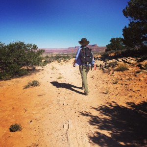 woman hikes in the desert surrounded by juniper trees