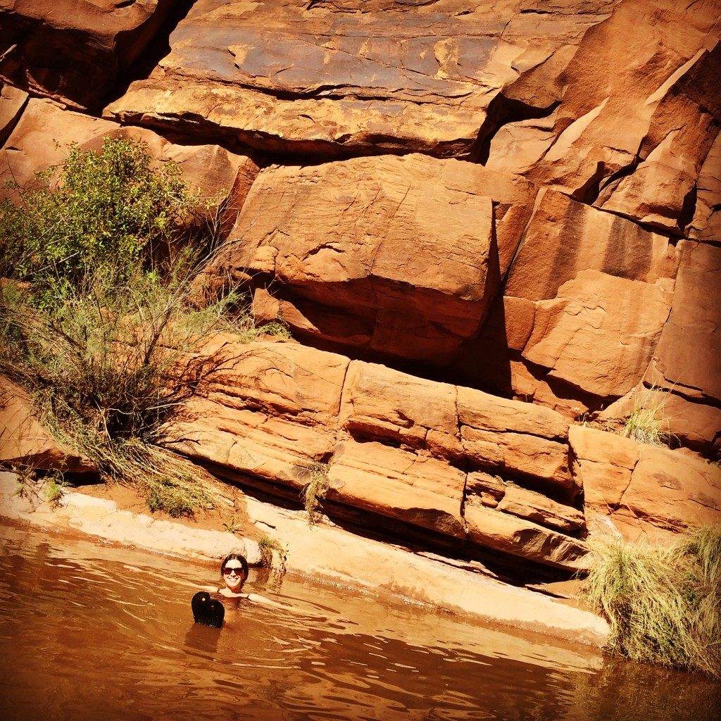 woman goes for a swim in a swimming hole surrounded by red rock